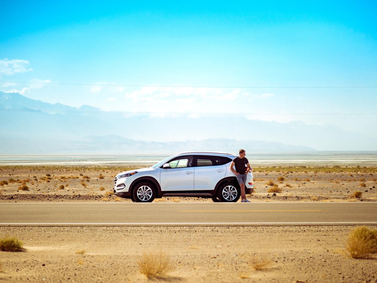 man standing by car in desert